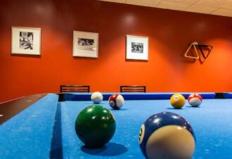 Close up of pool blue pool table looking at the bblack and white picture frames on an orange wall